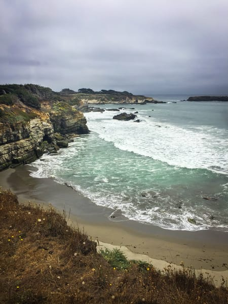 Waves break along the beach and cliffs of Gualala Point.