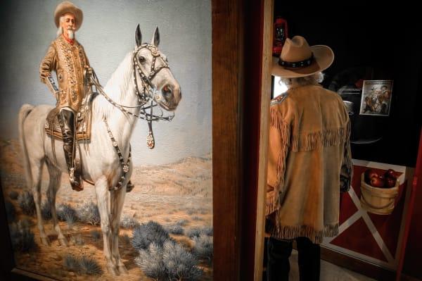 A Buffalo Bill impersanator walks past a Buffalo Bill painting