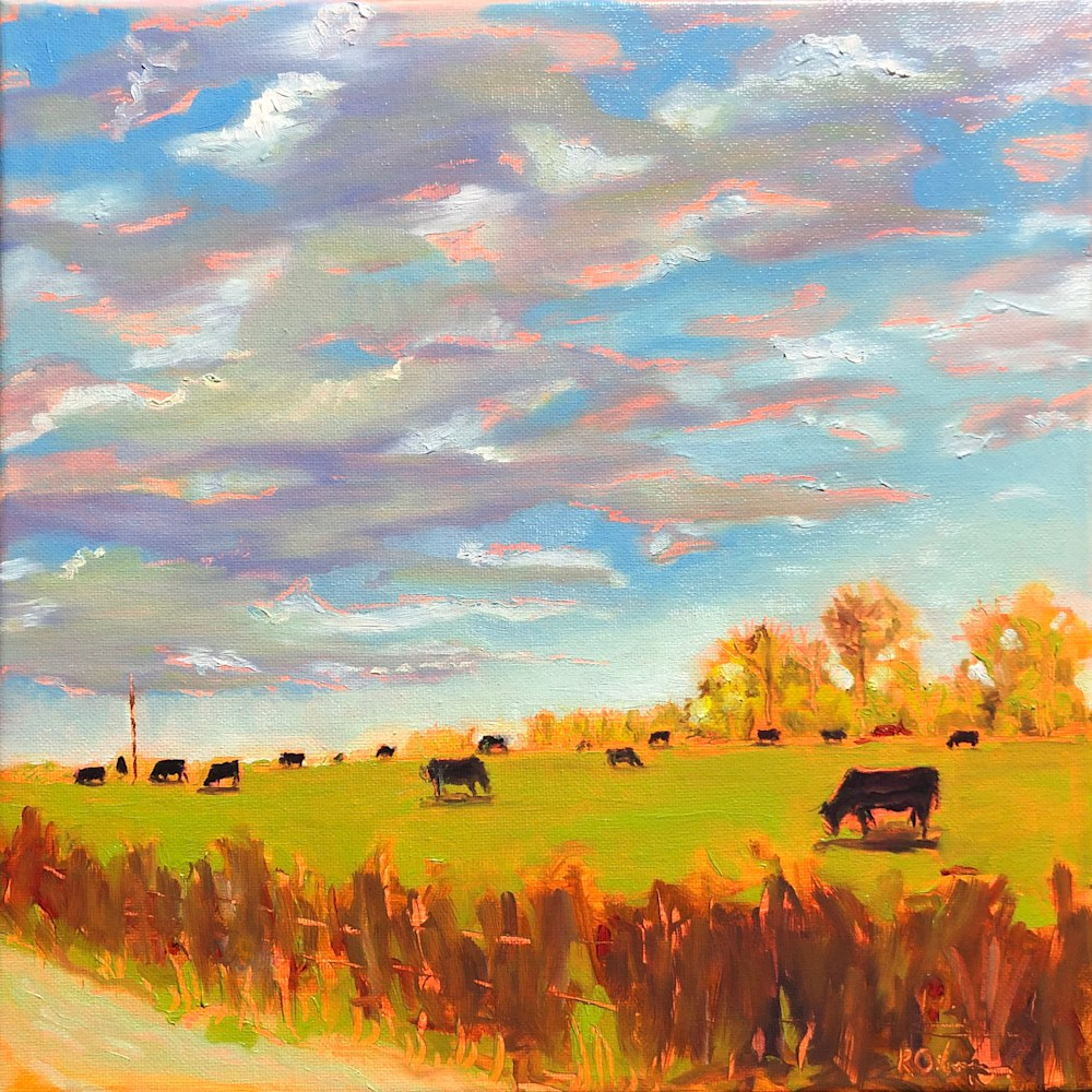 Cows Grazing under a Colorful Cloudy Sky