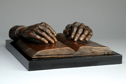 Faith - the hands of Mary McCormick resting on a Holy Bible - cast bronze