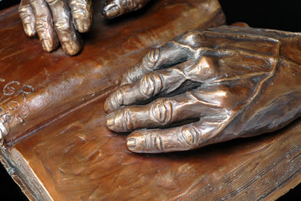 Faith - hands of Mary McCormick resting on a Holy Bible - cast bronze - close up