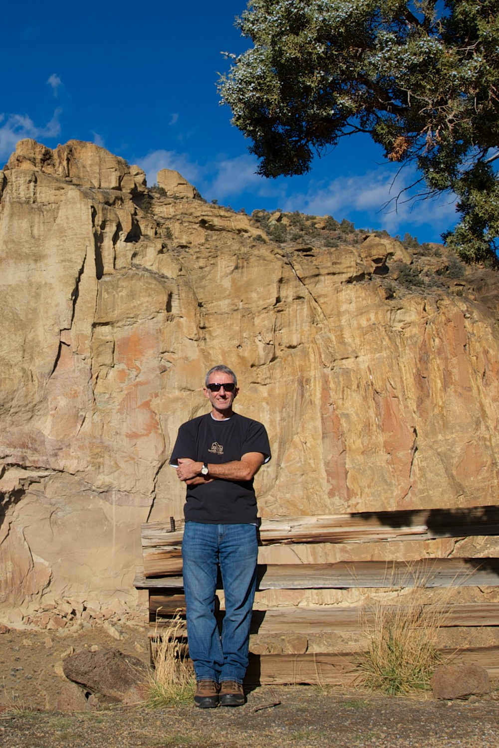 Photographer Shaun McGrath standing in front of a rock, tree and blue sky