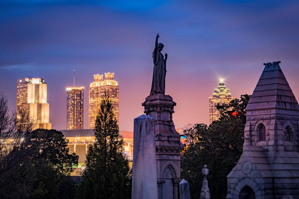 A Golden Hour photo of the City of Atlanta as backdrop to Oakland Cemetery
