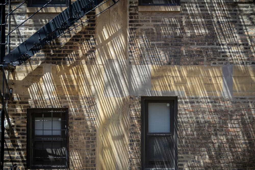 Shadows and light thrown on the wall from the fire escape