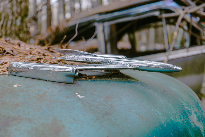 A hood ornament that looks a little like an airplane from an old car at Old Car City USA