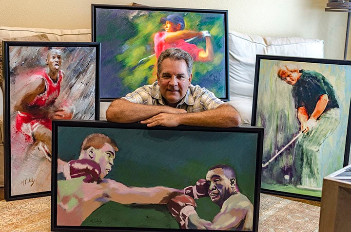 Sports artist Mark Trubisky standing next to his paintings.