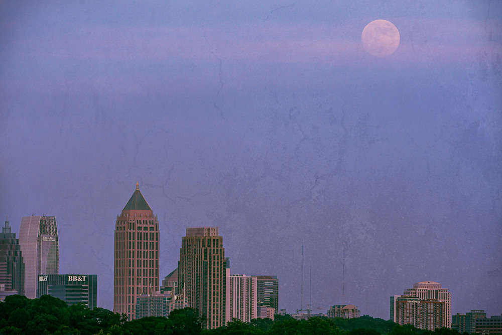 A pretty blue hour photo of the moon rising over Atlanta