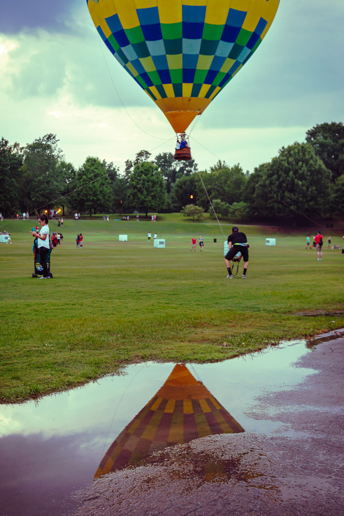 A hot-air balloon at Piedmont Park with a reflection in a puddle