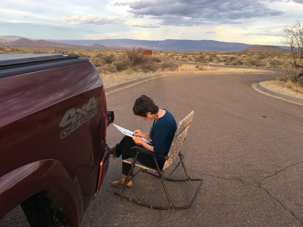woman painting in lawn chair by truck