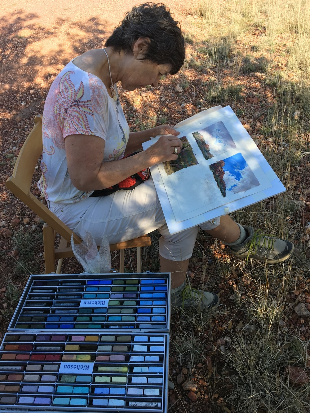 artist painting outdoors with miniatures in her lap