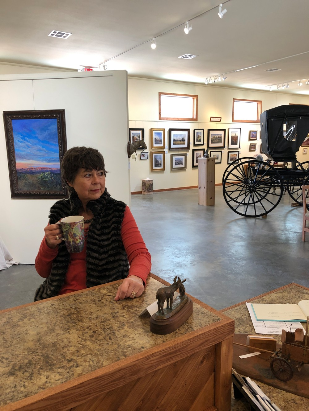 artist drinking coffee in gallery with wagons