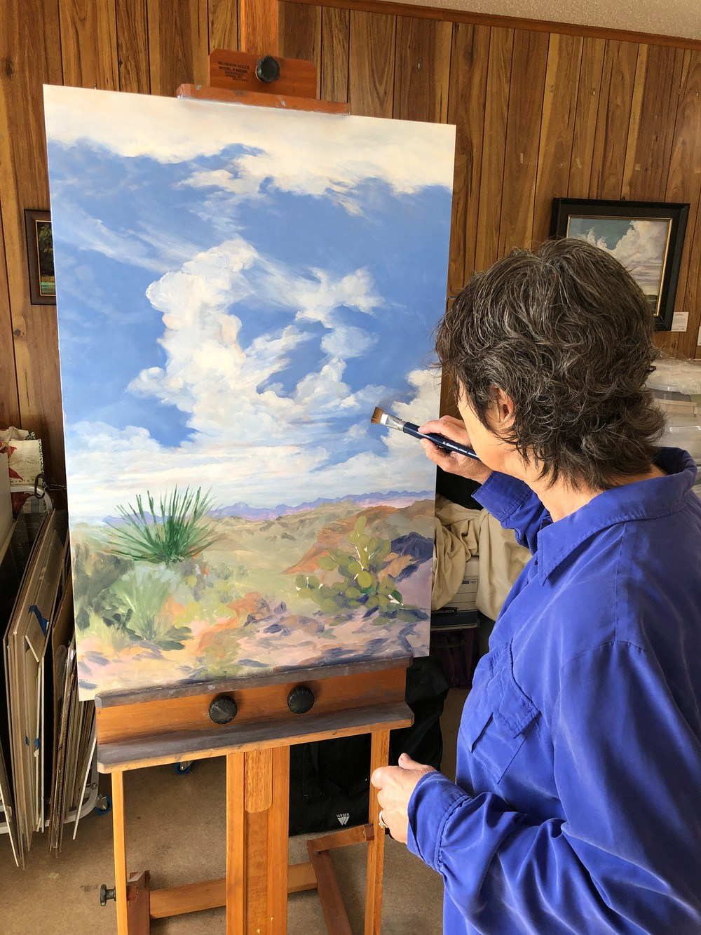 artist painting a landscape on large canvas