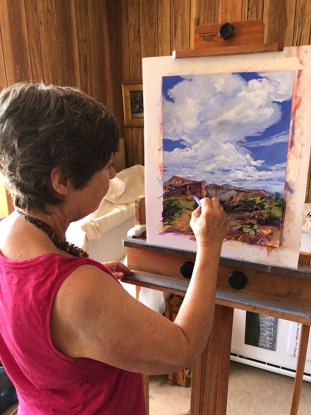 Artist Lindy Severns at easel working on a pastel painting