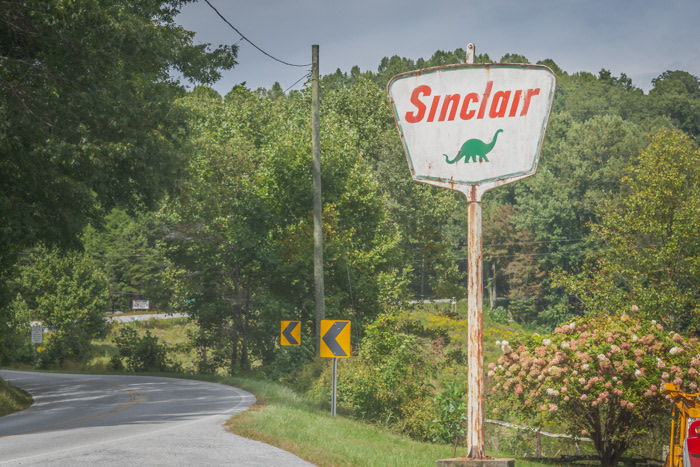 An old Sinclair Oil sign along the road