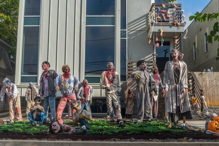 Some zombies decorating a lawn for Halloween