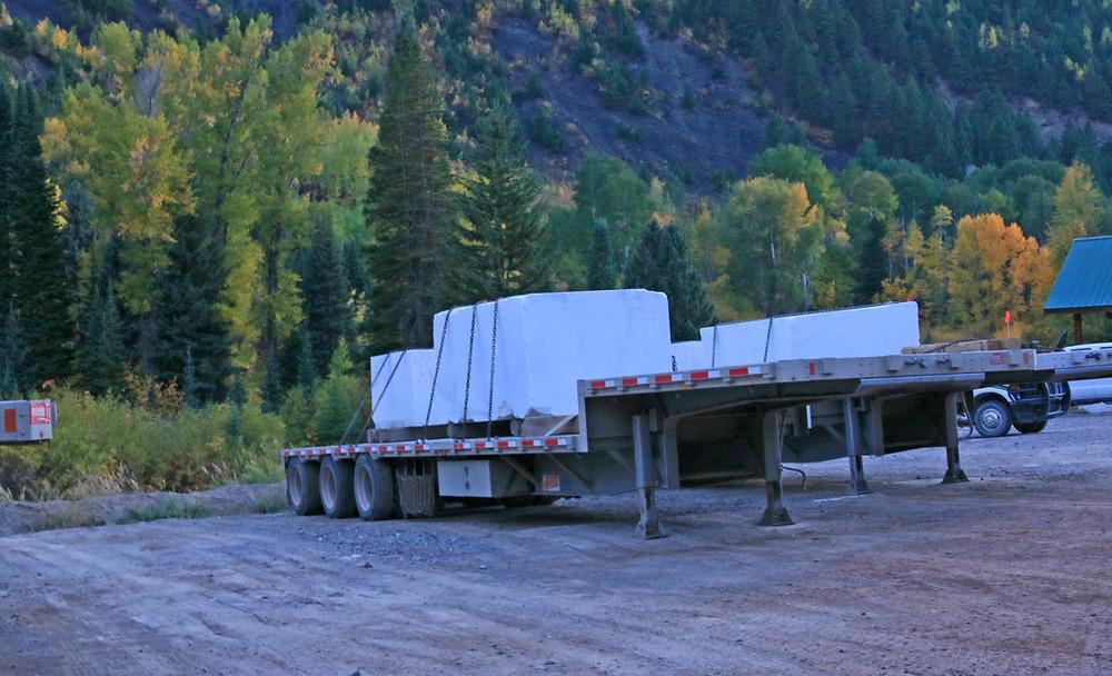Huge marble slabs loaded on a flatbed trailer.