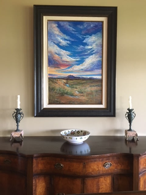 framed Lindy Severns oil painting hanging above table