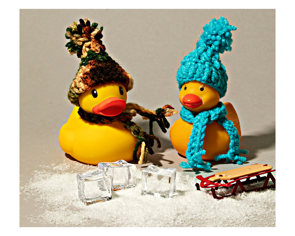 two rubber ducks with crocheted hats and scarves