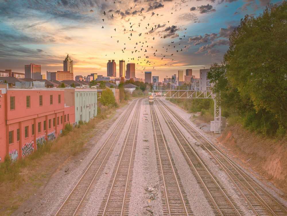A flock of birds flying into the sunset with railroad tracks in the foreground and the city of Atlanta in the background