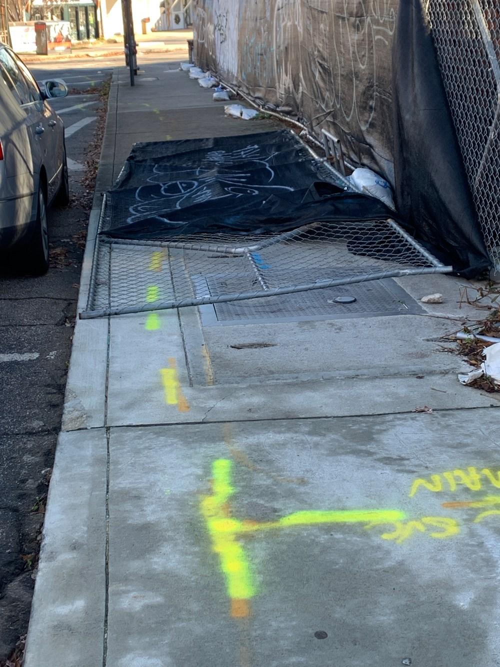 Chainlink fence fallen across the sidewalk in Atlanta