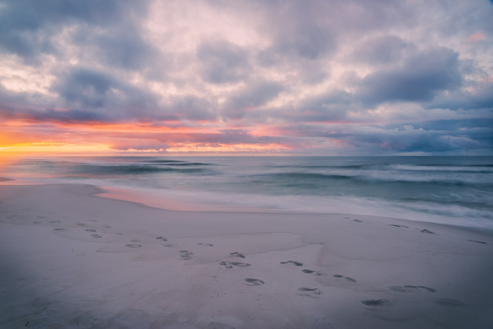 A beautiful sunrise over the ocean in Destin, Florida with the sandy beach in the foreground