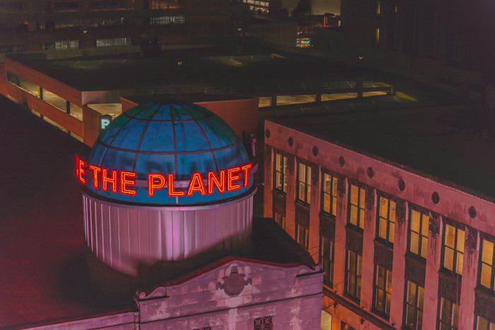 The Hard Rock Cafe sign on top of the building in Atlanta using fast shutter speed to freeze the words Save the Planet