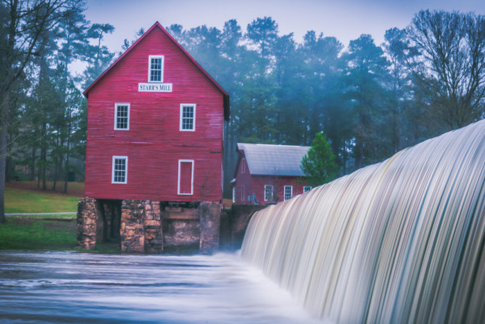 A photo of Starr's Mill at sunrise on a cloudy day