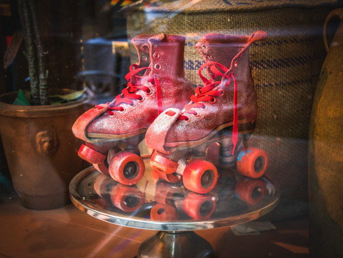 A pair of '70s roller skates in the window of a vintage store