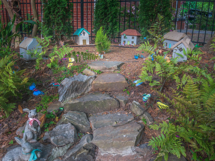 A little fairy garden in someone's yard with five little houses