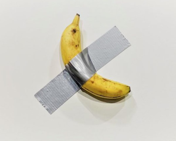 a banana duct-taped to a white wall