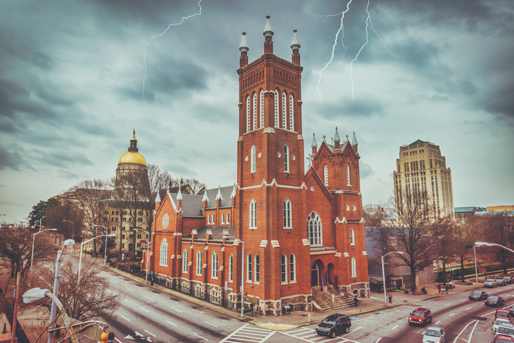 A photo of the Atlanta Capitol in the background with Immaculate Conception Catholic Church in the foreground. Stormy skies and lightening above the buildings. - Downtown Atlanta