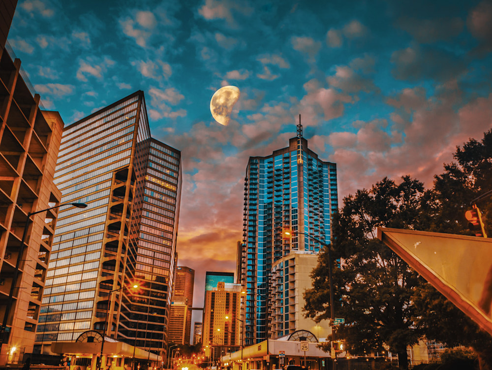 A composite art photo of the moon between some buildings in the City of Atlanta at sunrise