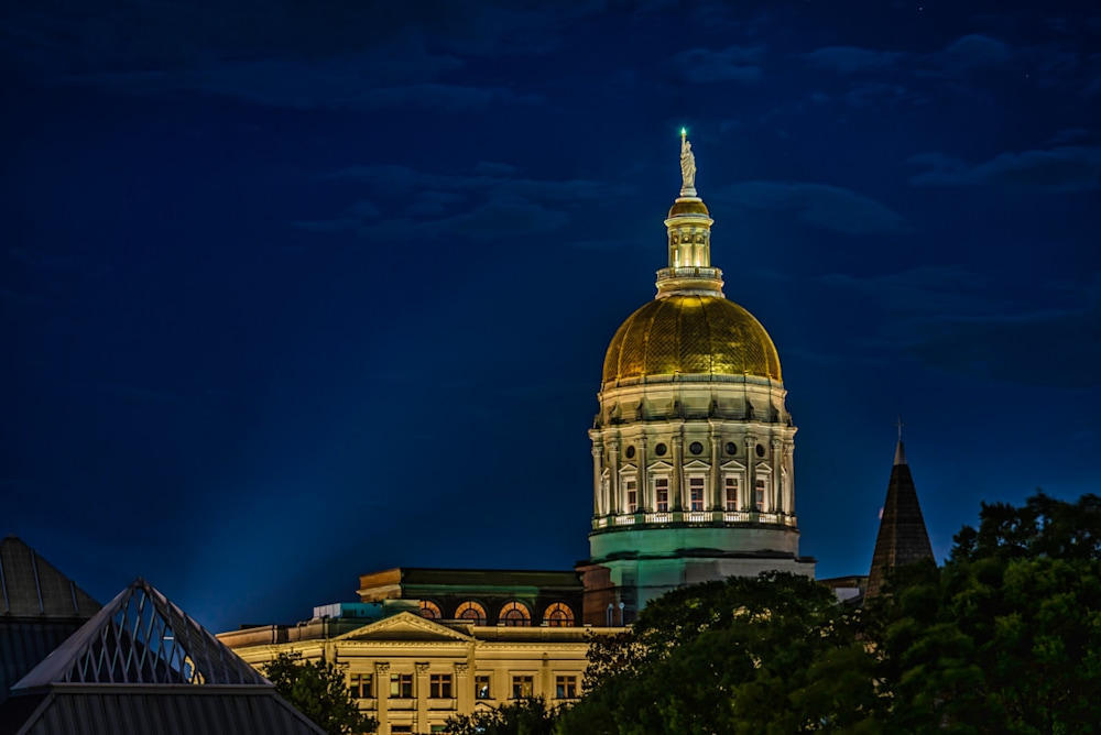 A spotlight shining on the gold dome of the Atlanta Capitol Building at night