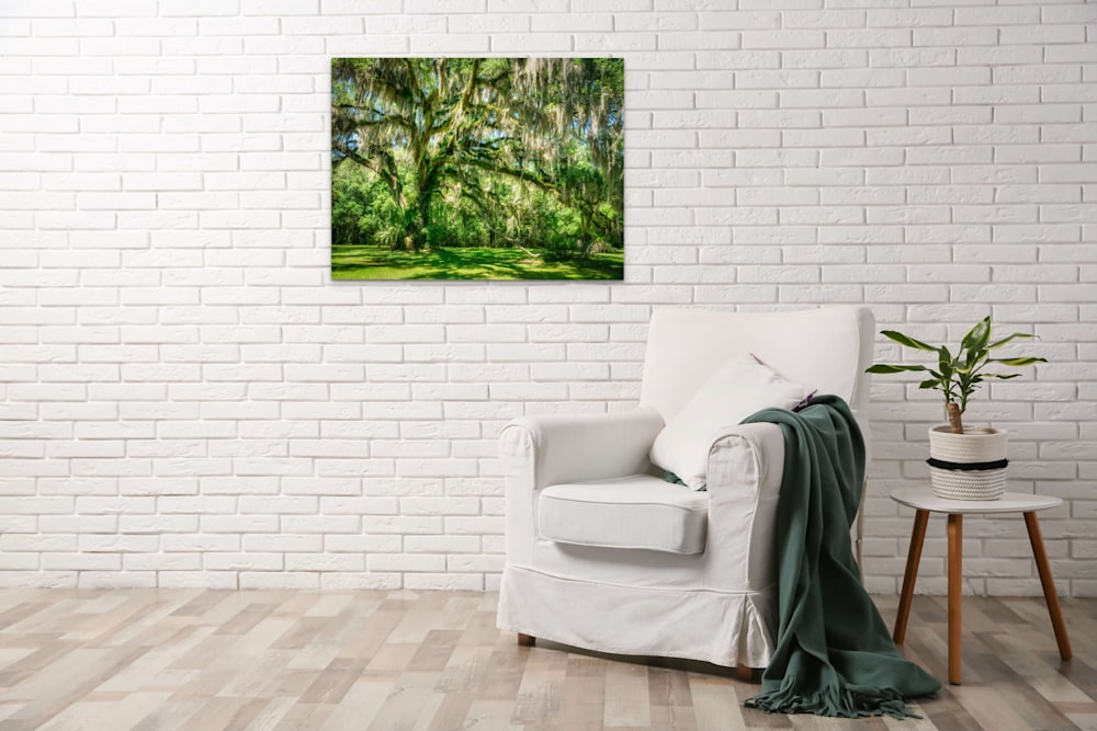 A beautiful green tree photographic print hanging in an all white room against a white brick wall