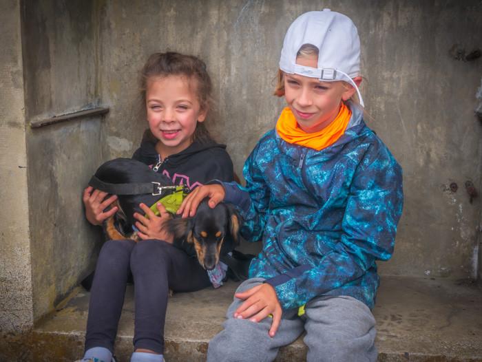 Young kids holding a mini-Dachshund