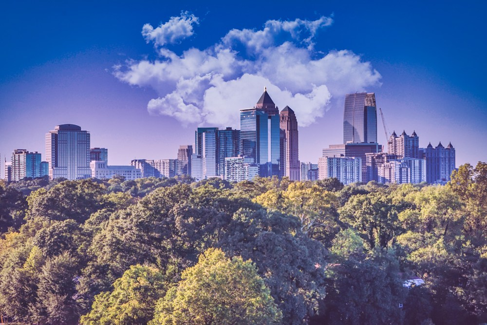 A little puff of white clouds over the City of Atlanta with tons of green trees in foreground. Photo was taken from up on a rooftop