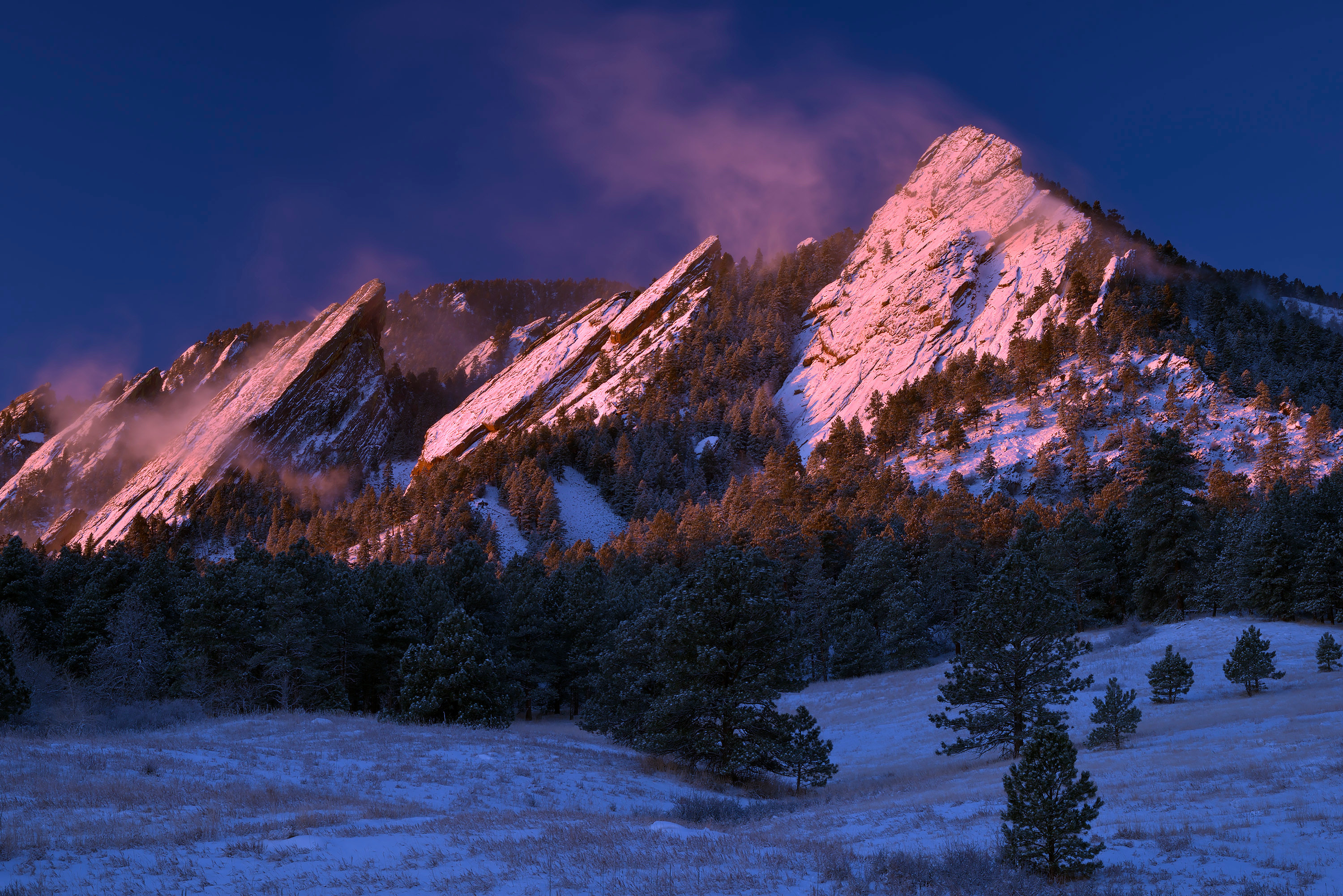 <div class='title'>           Winter Sunrise at the Flatirons         </div>                 <div class='description'>           Morning light bathes the Flatirons in pink after a fresh snowfall, while the wind whips snow into the air off of the rock faces. Purchase this photograph as a fine art print on paper, canvas, metal, or acrylic.         </div>