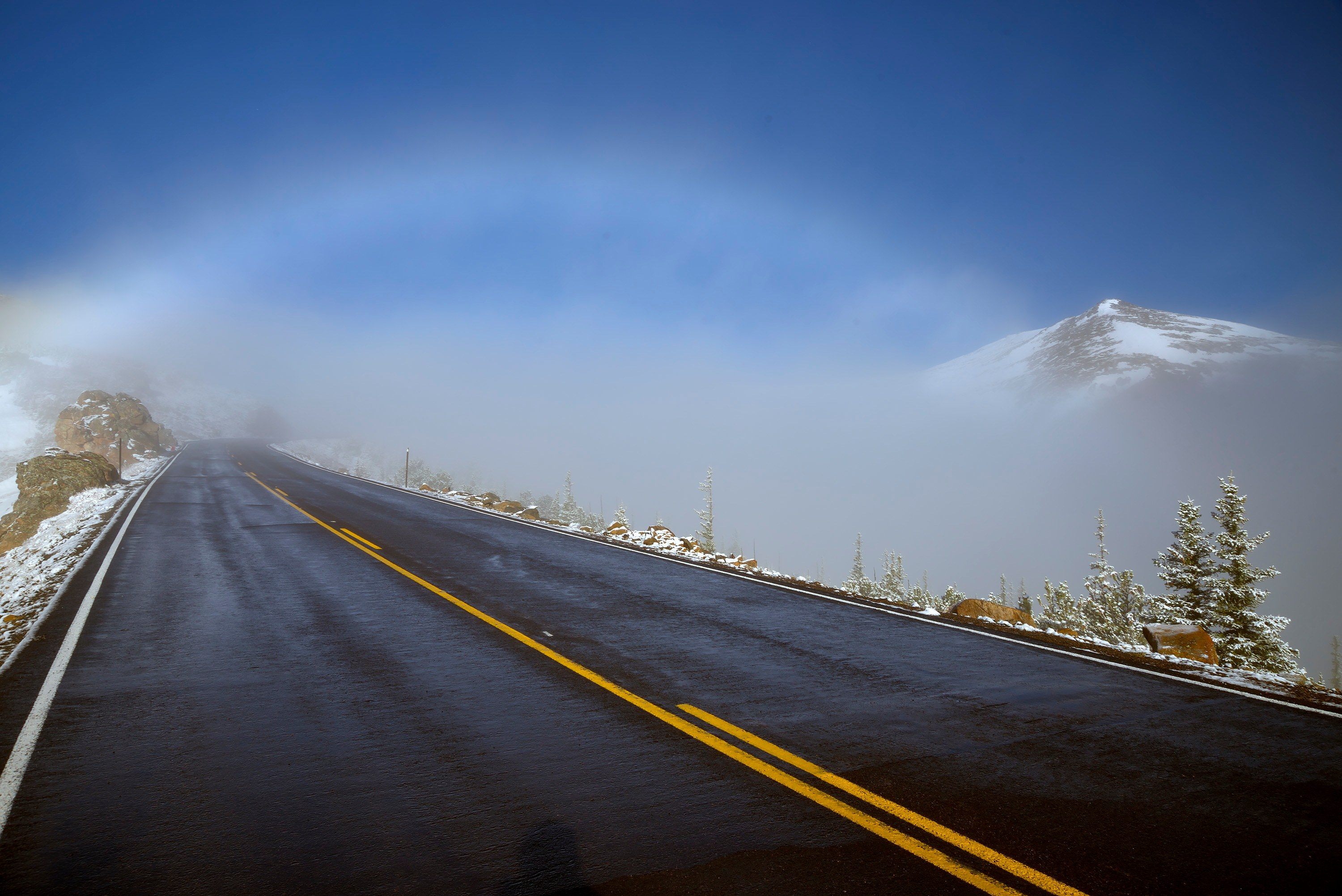 <div class='title'>           Gateway to the Mountains         </div>                 <div class='description'>           As I began to rise above the clouds, the sunlight shining through the dissipating clouds forms a cloud bow arcing over Trail Ridge Road as it rises above the trees.         </div>